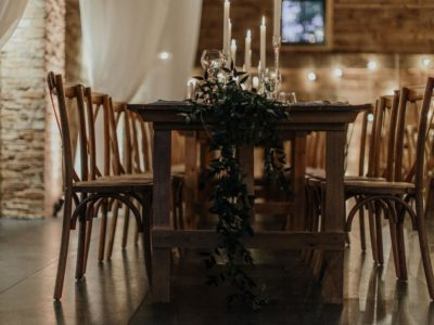 Beautiful rustic wooden cross back chairs with vintage trestle tables and foliage table decoration