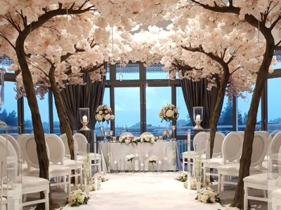 Elegant white Louis Dior chairs with floral wedding arch and large lanterns