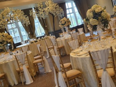 Gold Chivari chairs with ivory draylon seat pads and ivort chair drapes with elegant floral arrangements
