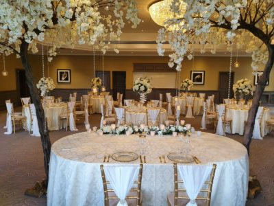 Gold chivari chairs with ivory seat pads and chair drapes gold wedding theme with huge floral trees