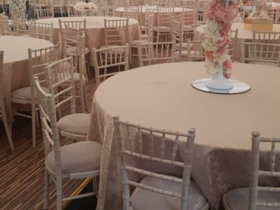 Limewash chivari chairs and ivory draylon seat pads in elegant marquee with flower arch and candelabra