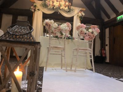 Limewash chivari chairs for bride and groom with floral chair decoration and rustic lantern