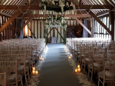 Limewash chivari chairs in rustic wedding barn and rose petals along the aisle