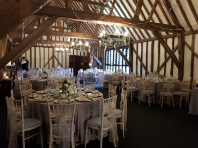 Limewash chivari chairs in rustic wedding venue with floral chandeliers and twinkling wedding lights