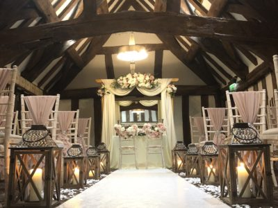 Limewash chivari chairs with blush chair drapes and rustic lanterns in rustic barn theme