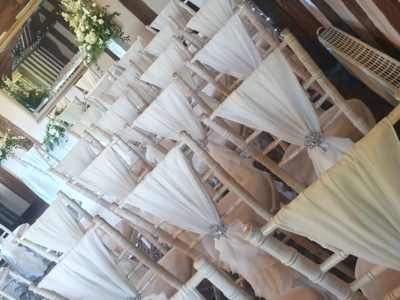 Limewash chivari chairs with ivory draylon seat pads and chair drapes and silver brooches
