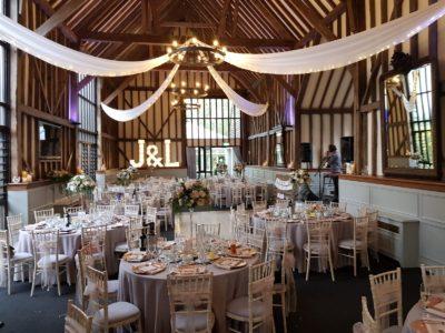 Limewash chivari wedding chairs in a beautiful wedding barn with ceiling drapes
