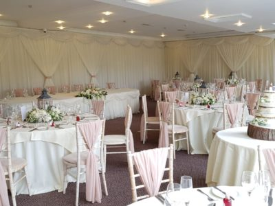 Lovely limewash chairs with blush pink chair drapes & rustic flowers and wedding cake