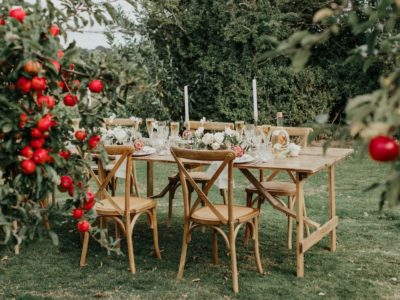 Natural weathered oak cross back chairs in rustic garden setting