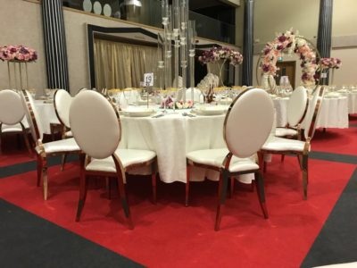 Rose Gold Louis Dir chairs with large floral arrangements wedding chairs