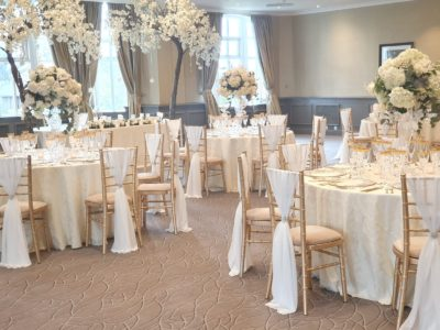 Stunning gold chivari wedding chairs with ivry draylon seat pads and large ivory and gold floral arrangements
