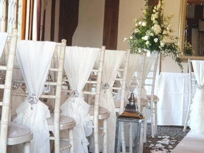 Stunning limewash chairs with ivory seat pads and chair sashes and brooches