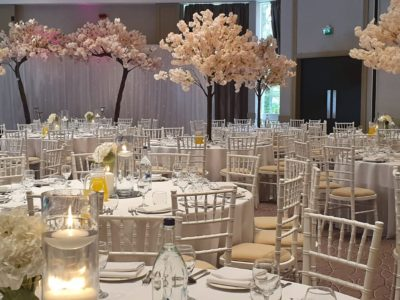White chivari chairs with ivory seat pads and pale pink floral trees
