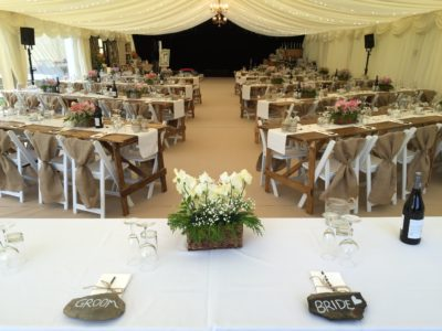 White folding ceremony wedding chairs and rustic tresstles