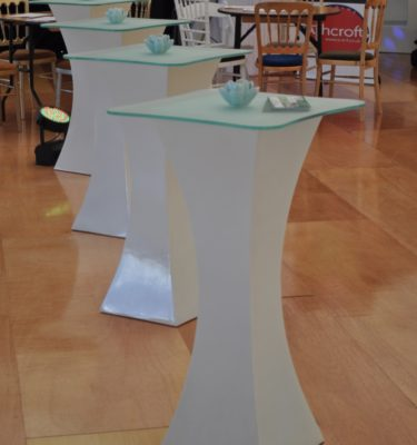 White poseur tables with glass tops