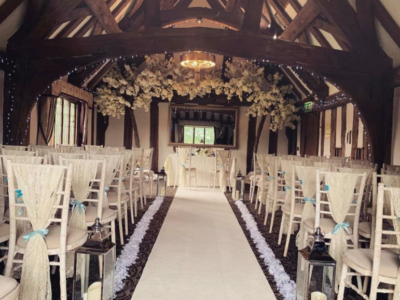 Limewash chivari chairs with drapes along wedding aisle