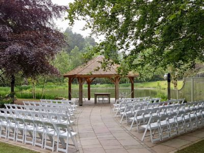 White ceremony folding chairs outside wedding ceremony by river